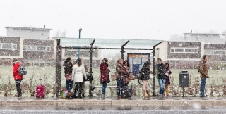 Wachten bij de bushalte in de sneeuw